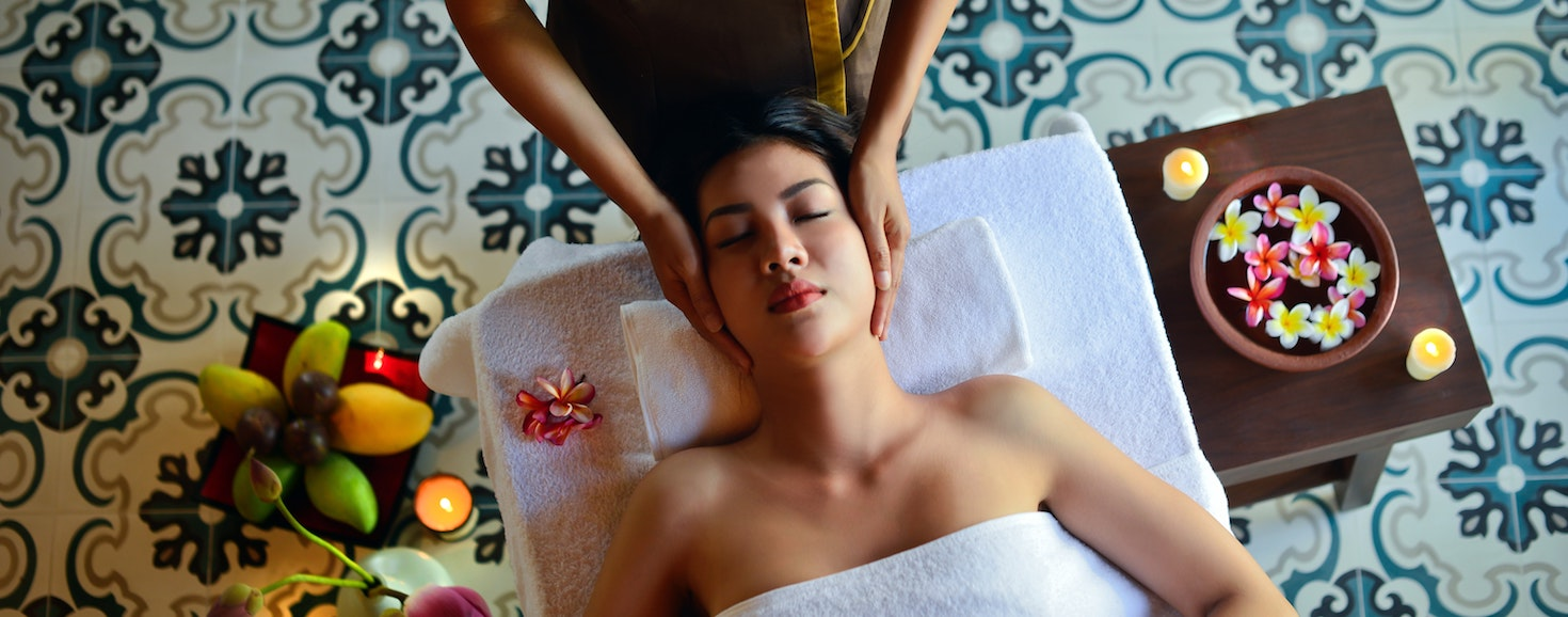 a massage for a woman in a spa tends 2020